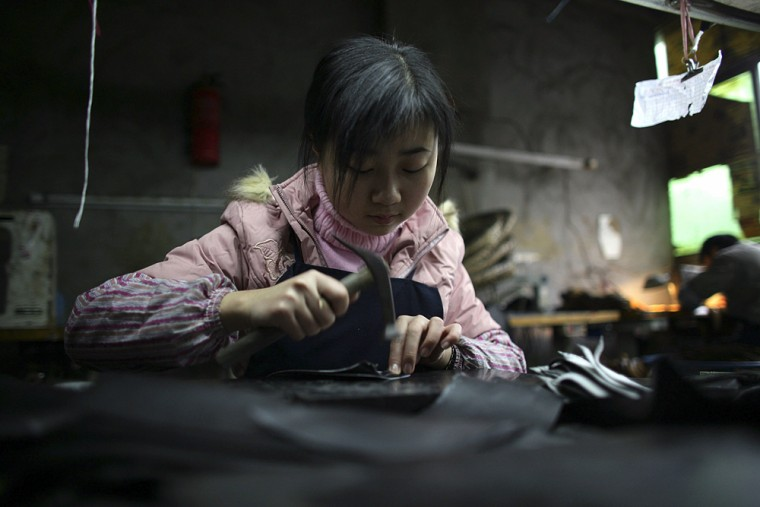 Image: A worker labors at a shoe factory in China