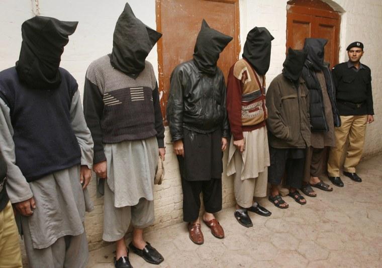 Image: Police showcase six hooded men