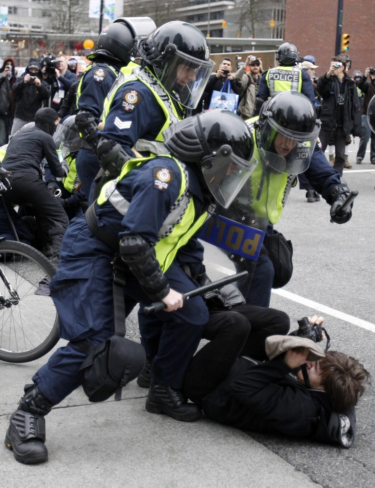 Image: A demonstrator takes pictures of policemen attempting to detain him during a protest in downtown Vancouver against the Vancouver 2010 Winter Olympics