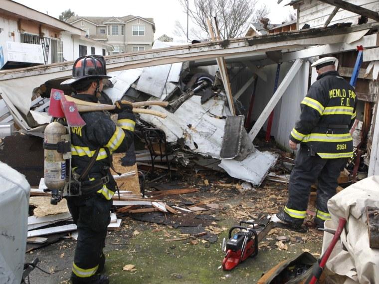 Image: Menlo Park firemen look at the scene of a small plane crash