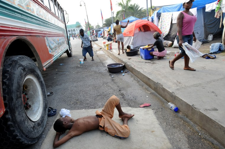 Image: A Haitian boy rests next to a camp set up in front of the Presidential Palace in downtown Port-au-Prince