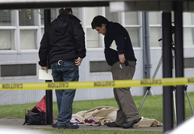 Image: Forensics investigators view the blanket-covered body of a special education teacher