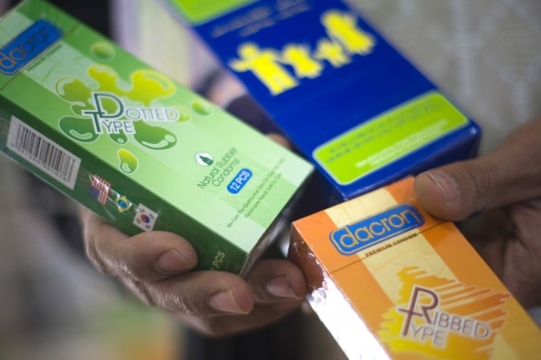 Image: A pharmacologist shows packs of condoms at a pharmacy in Herat