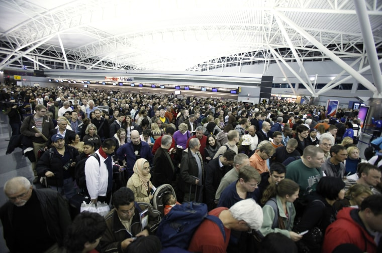 Image: Airline passengers wait to re-enter Terminal 8 at the John F Kennedy International Airport