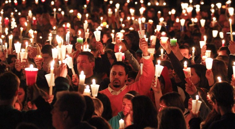 Image: People attend a candlelight vigil held at St. Michael's Catholic Church