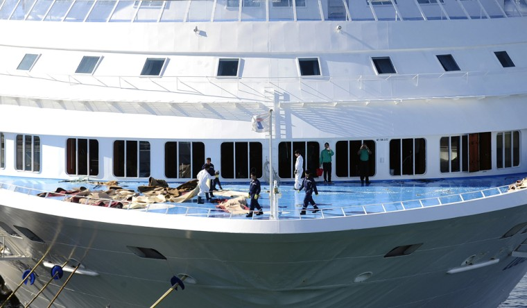 Image: Workers clean up broken windows on the Cypriot-owned Louis Majesty cruise ship