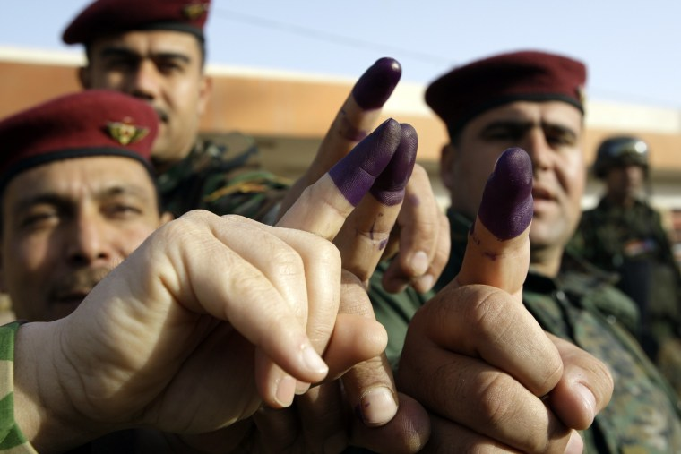 Image: Iraqi soldiers show their ink stained fingers after casting their votes