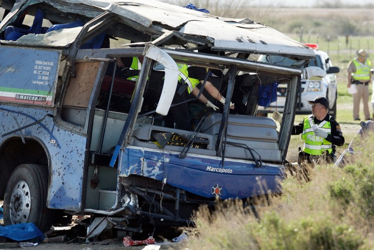 Image: police officers look through the wreckage of a tour bus after a multi-car crash
