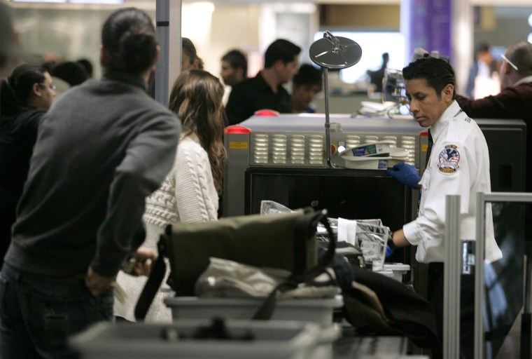 Image: A U.S. Transportation Security Administration agent looks at the baggages of airline passengers at a security checkpoint at San Francisco International Airport in California