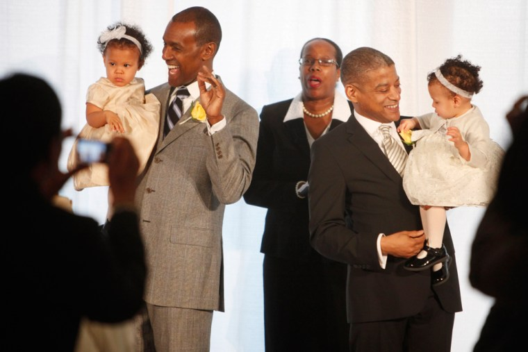 Image: Rocky Galloway, left, and Reginald Stanley hold their twin daughters after they were married