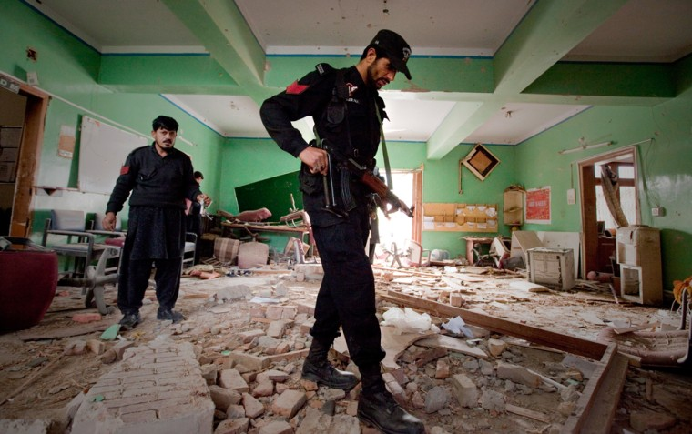 Image: Policemen inspect the destroyed offices of aid group World Vision in Oghi