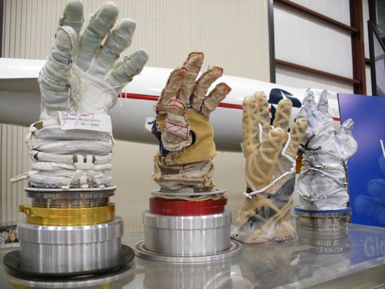 From left to right: NASA's Phase VI spacesuit glove and entries in NASA's 2007 Astronaut Glove Challenge from the MDLH team, artist Theodore Southern and engineer Peter Homer.
