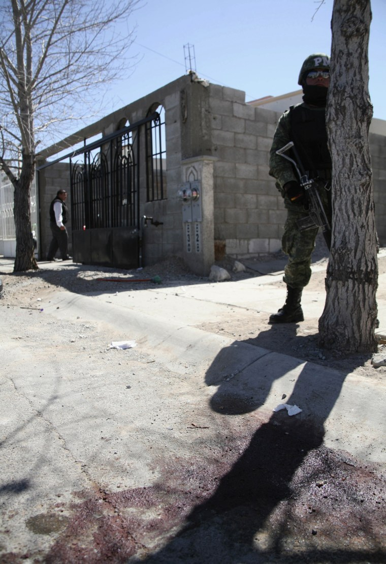 Image: A soldier stands guard outside a house where several people were killed in Ciudad Juarez