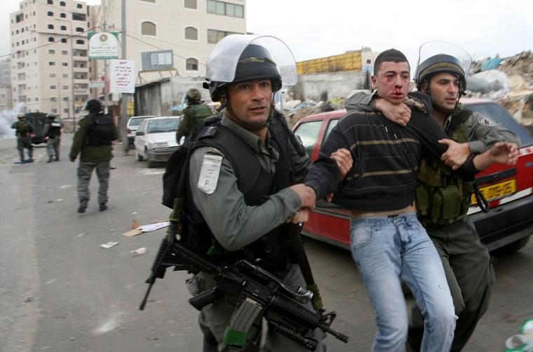 Image: Israeli border policemen arrest a Palestinian protester during clashes at the Shuafat refugee camp in Jerusalem