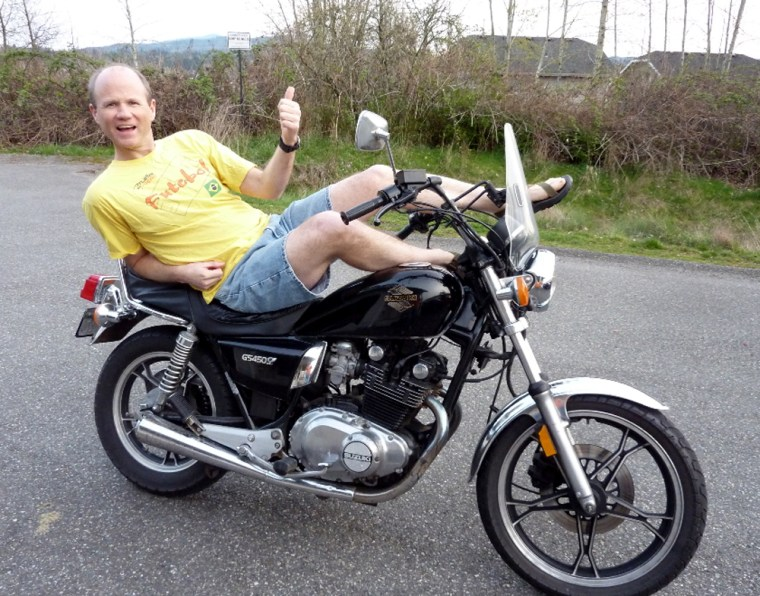 """Bellingham Christian School Principal Bob Sampson lounges on his motorcycle at his home on Tuesday. Sampson canceled classes at the private school on Wednesday for a """"sun day."""""""