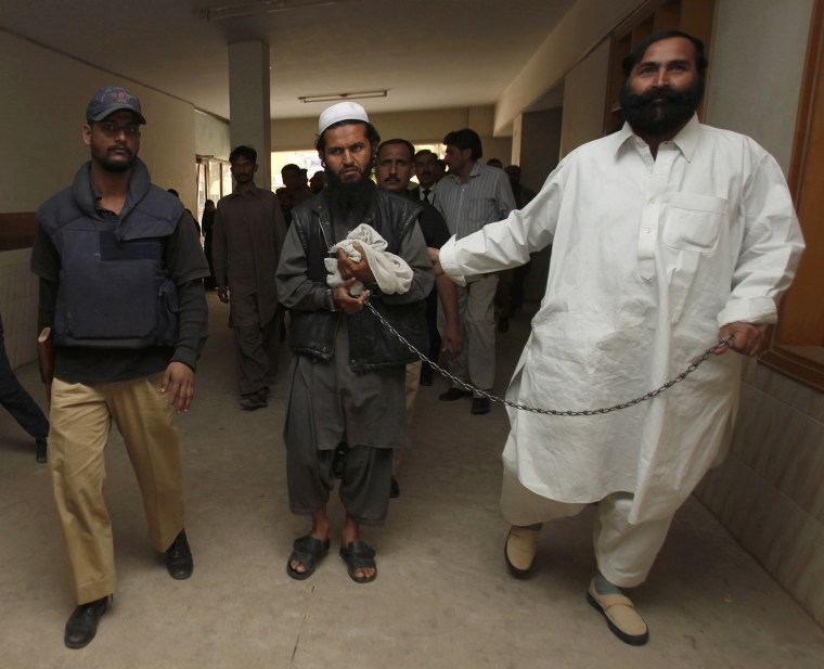 Image: Police escort a man, who was arrested a day earlier, through the halls of a district court where he will appear before a judge in Karachi