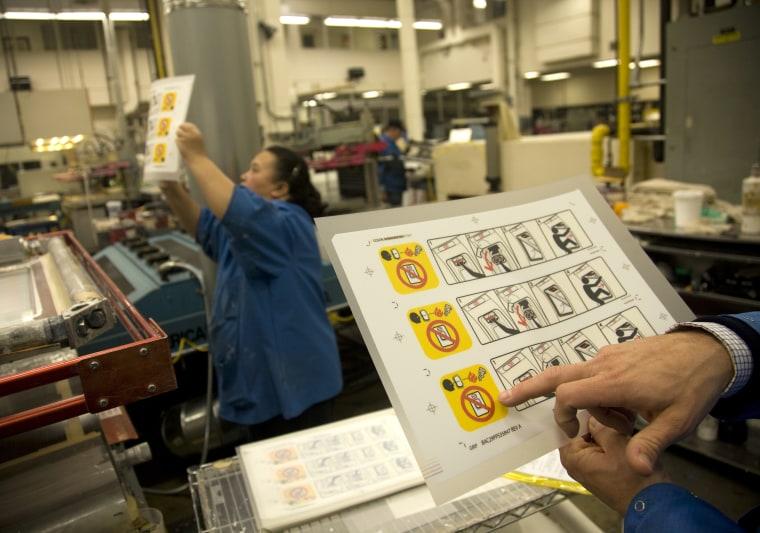 Image: Engela Vang looks at Boeing stickers