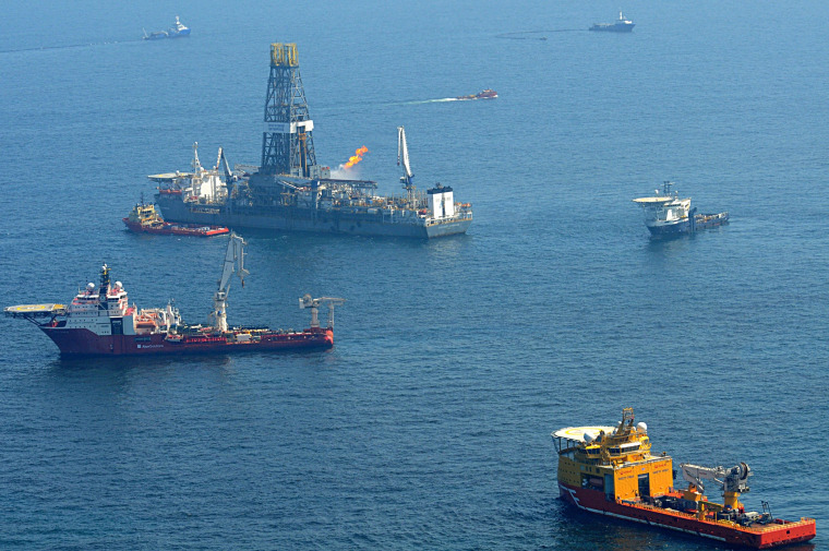 Image: Offshore supply vessels assist and observe the worksite of the Deepwater Horizon oil rig