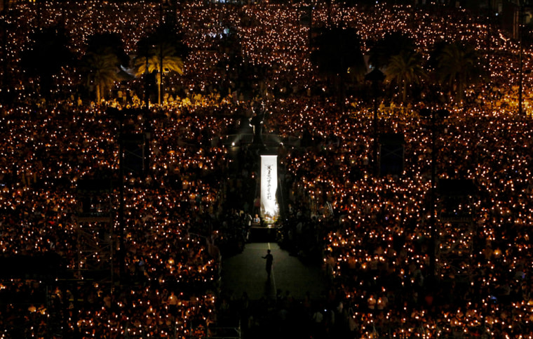 Image: Tens of thousands of people attend a candlelight vigil at Hong Kong's Victoria Park