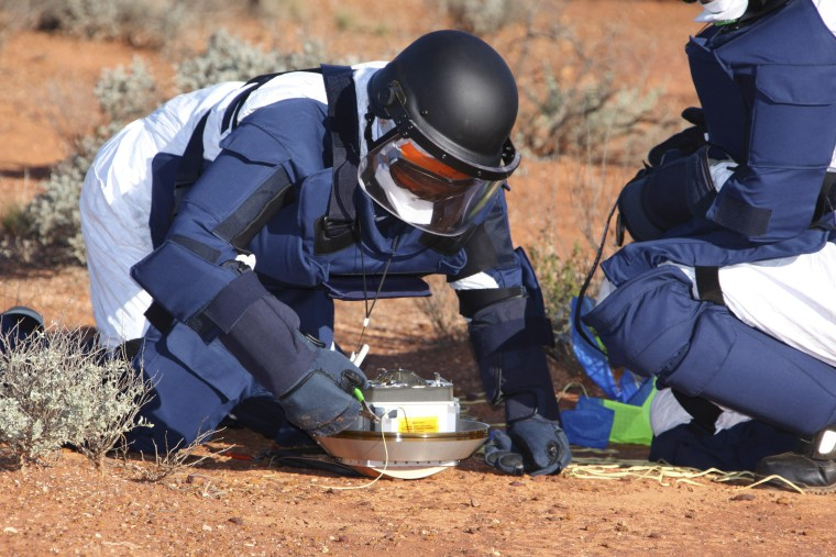 Image: A person conducts safing treatment to the Japanese Hayabusa Sample Return Capsule (SRC) at Woomera rocket range