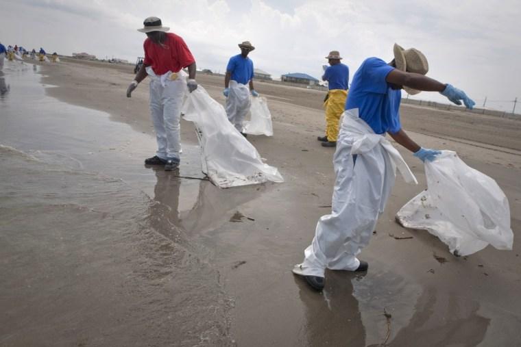 Image: BP workers pick up tar balls
