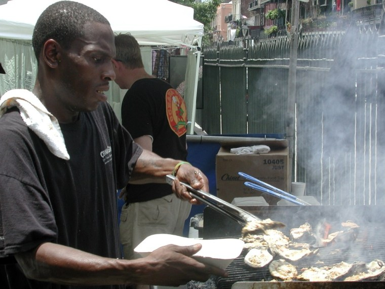 Image: DeShawn Harris of Oceana Restaurant grills oysters at the Louisiana Seafood Festival in New Orleans.