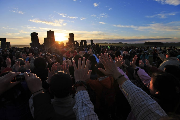 Image: People raise their hands while meditating during the summer solstice at Stonehenge