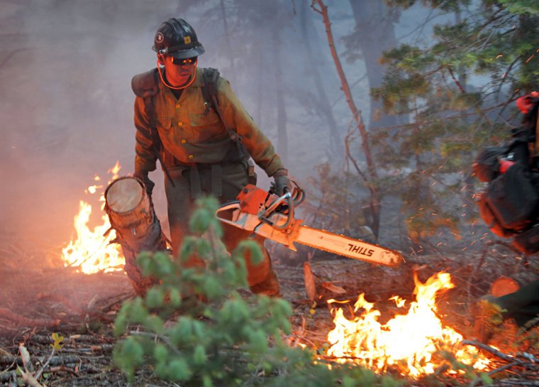 Image: James Honanie, of the Flagstaff Hot Shots, removes fuel from the path of the Schultz Fire