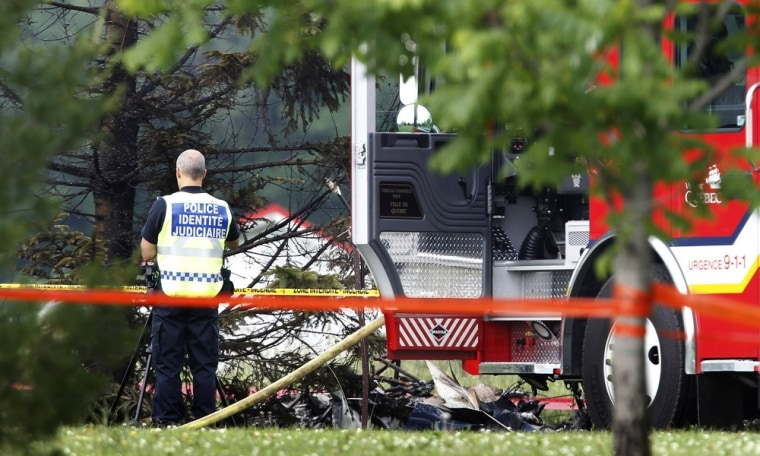 Image: A police officer looks at what is believed to be the remains of an airplane after a crash in Quebec City