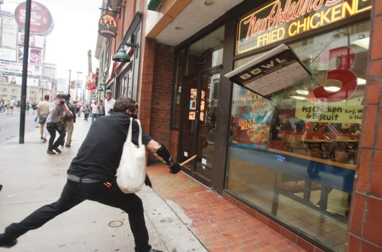 Image: A protester smashes a window in the Toronto's downtown core