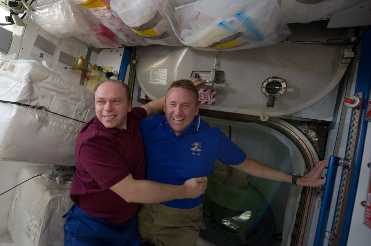 Russian cosmonaut Oleg Kotov, commander of the International Space Station, embraces NASA shuttle commander Ken Ham during a farewell ceremony toward the end of Atlantis' visit to the outpost in May. The space station serves as an example of successful international cooperation in space — but not for the reasons many think.