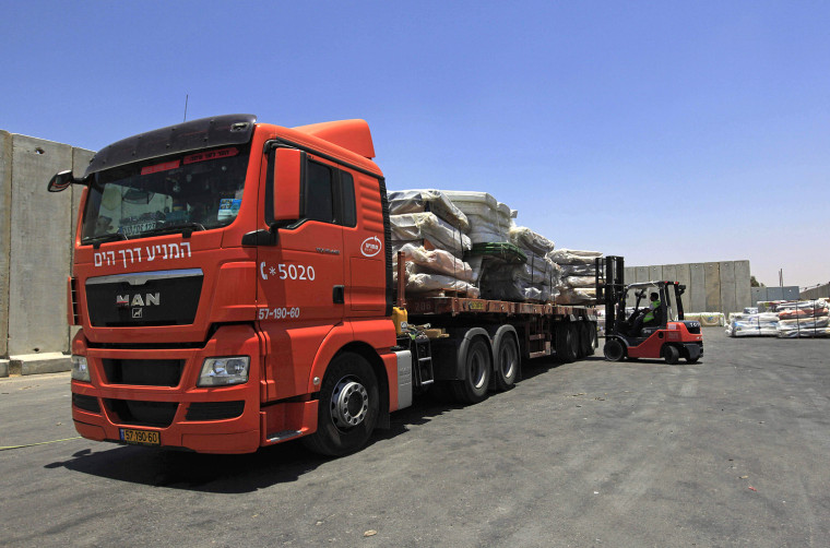 Image: An Israeli worker unloads goods from a truck at Kerem Shalom terminal