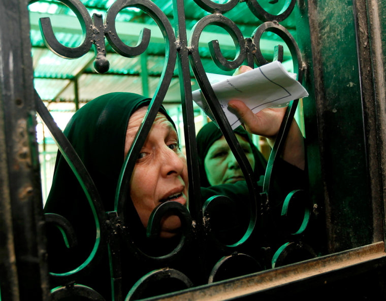 Image: Iraqi widow waits to receive money from a government office in Baghdad