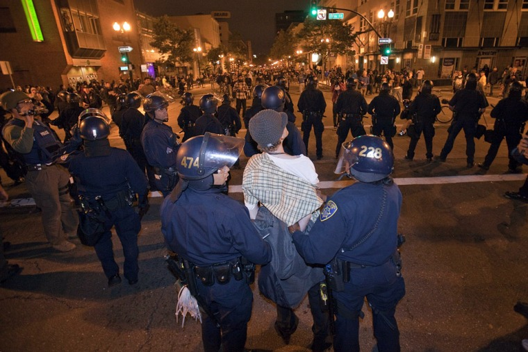 Image: A demonstrator is held by police as demonstrators face off with riot police in downtown Oakland
