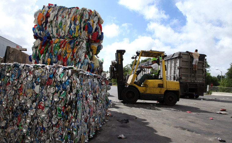 Image:  A forklift operator stacks bales of sorted recyclable materials.