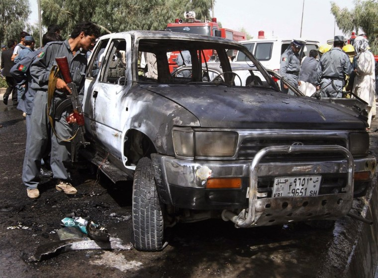 Image: Afghan policeman inspects a damaged vehicle
