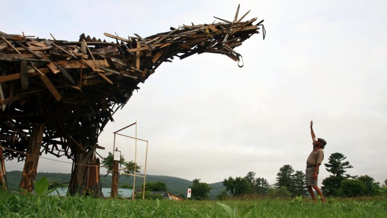 """Image: In this photo taken Friday, July 9, 2010, Brian Boland, 61, a former teacher, hot-air balloon designer and balloon pilot who runs the rural Post Mills Airport in Thetford, Vt., stands with his """"Vermontasaurus"""""""