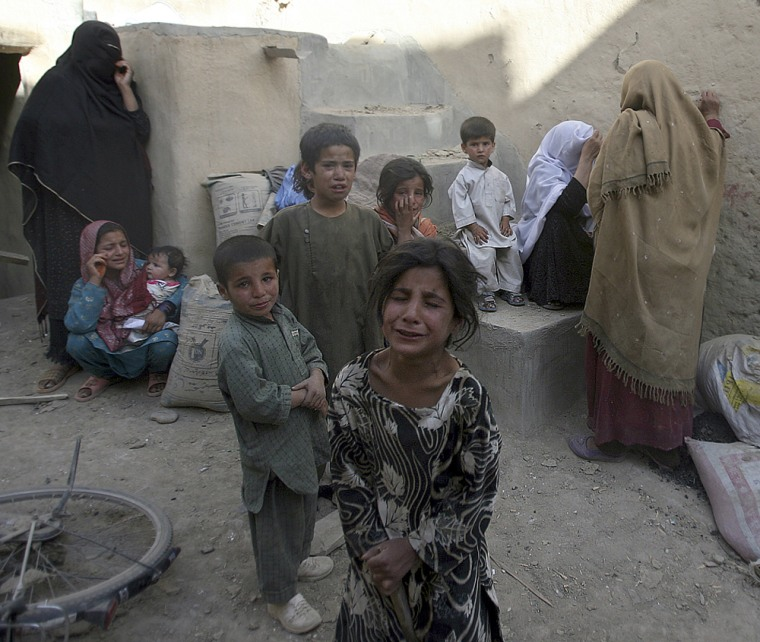 Image: Afghan children are terrified after they hear the blast of a controlled explosion near their house in Ghazni province south of Kabul