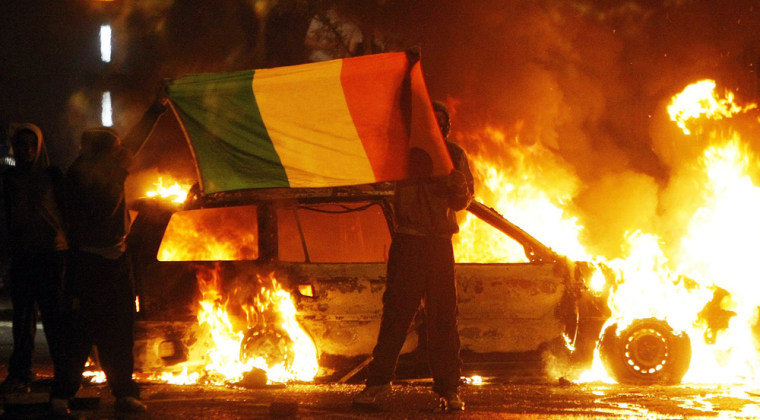 Image: Nationalist protesters brandish the Irish tricolour flag during clashes with police in Belfast