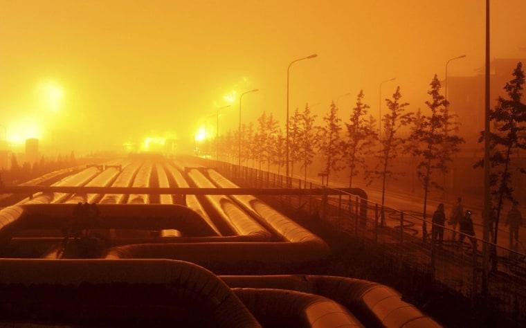 Image: Firefighters walk near an oil pipeline blast site in Dalian