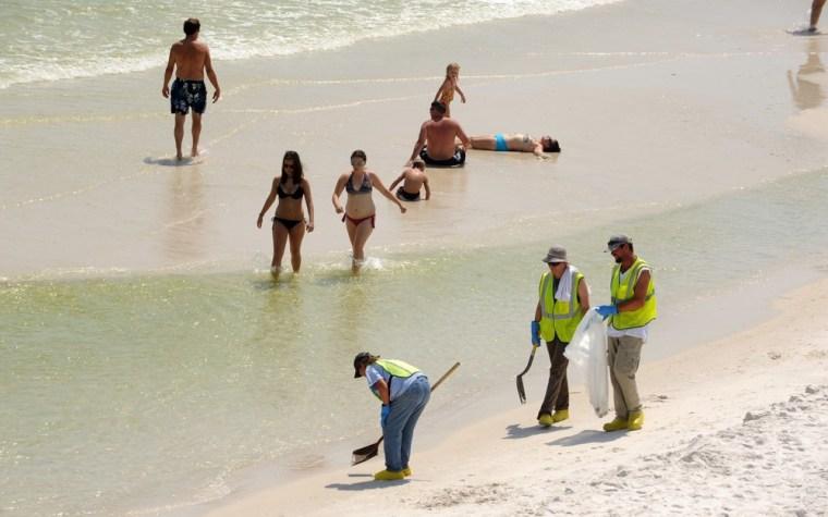 Image: Clean-up crews on Pensacola Beach, Fla.