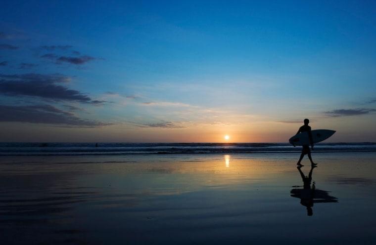 Image: Surfer on Playa Carmen beach at sunset.