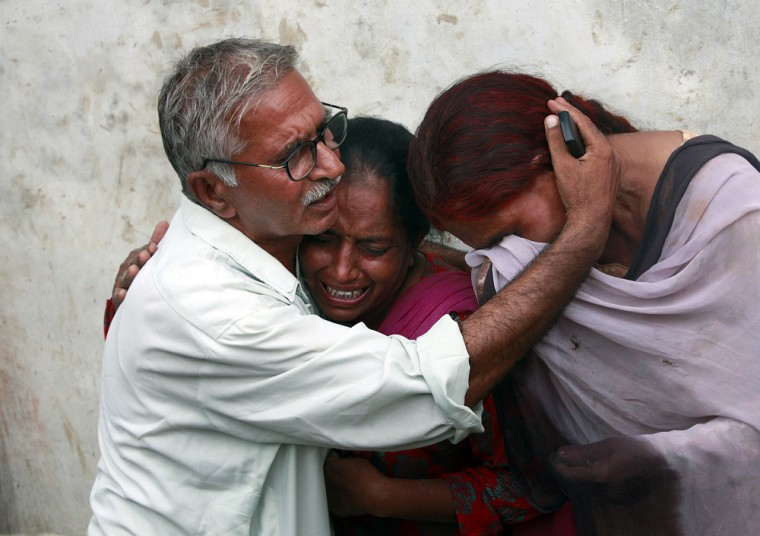 Image: A man consoles his family members after they returned to find their homes destroyed after heavy floods in Nowshera