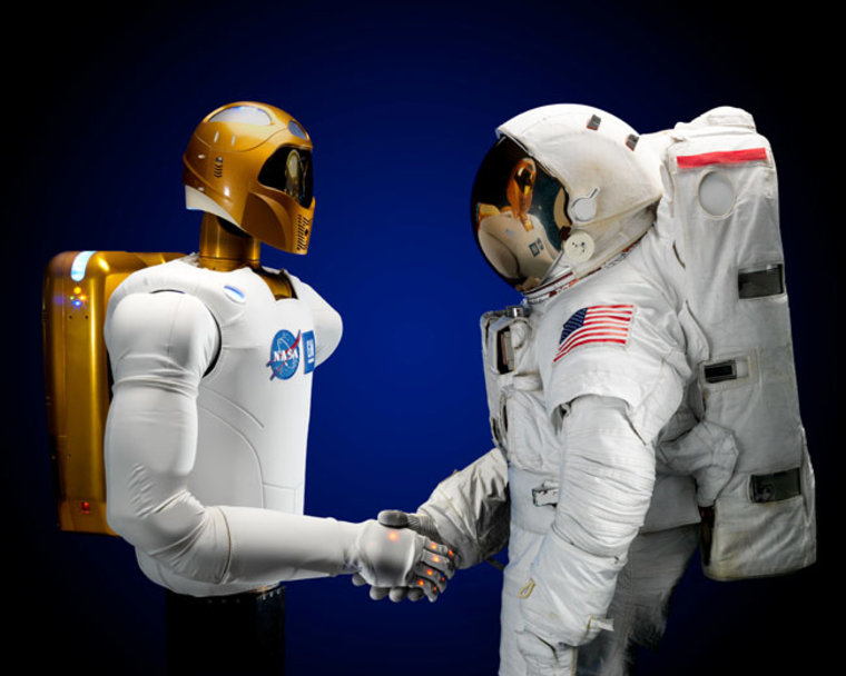 Image: Robonaut 2 shaking hands with astronaut in space suit