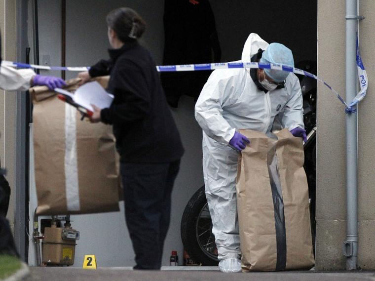 Image: Forensic police gather evidence at a crime scene near Slateford Road in Edinburgh, Scotland where three children died