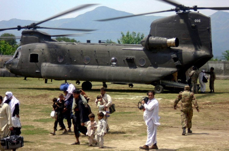 Image: People who had been stranded in Kalam, arrive in Khawaza Kheila in northwest Pakistan, on the U. S. Chinook helicopters