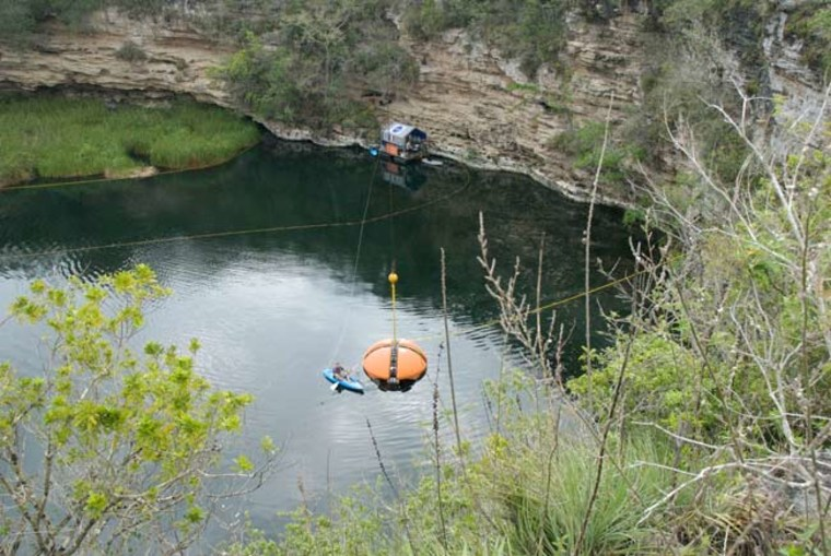 Image: Large orange DEPTHX robot floats in water with kayaker nearby