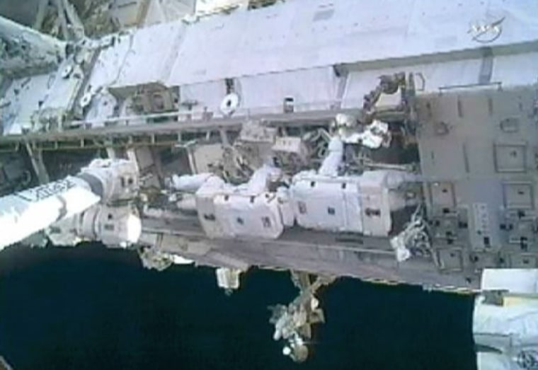 Image: Doug Wheelock and Tracy Caldwell Dyson work head to head to remove a faulty ammonia pump module on the exterior of the International Space Station during their spacewalk