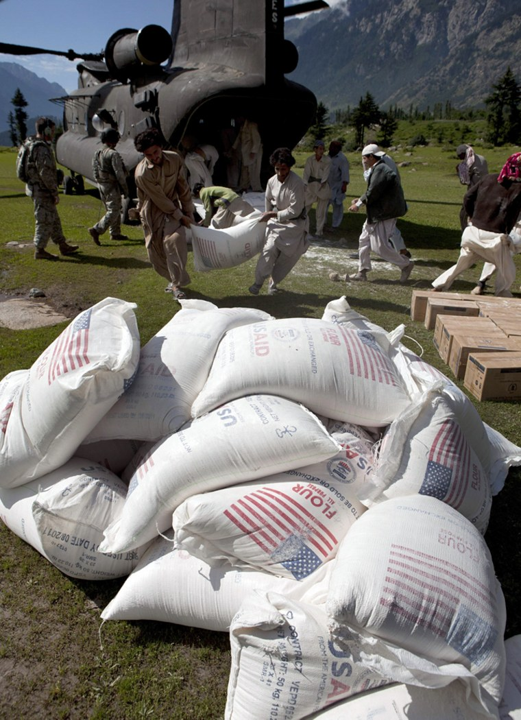 Image: Volunteers carry a sack of flour provided by the U.S. government in Pakistan's Swat valley