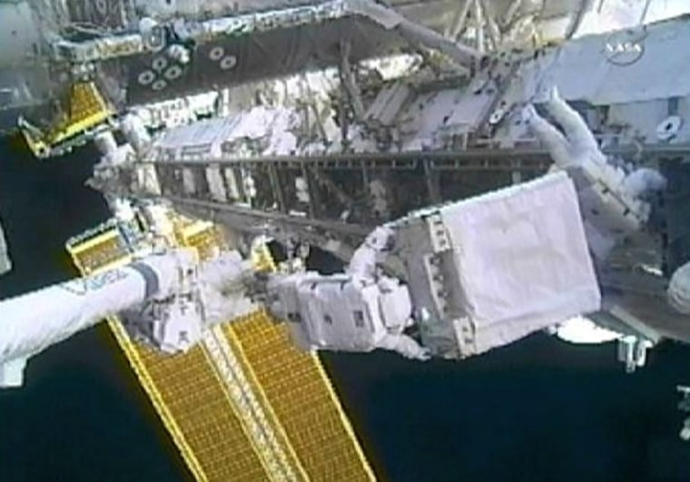 Image: Spacewalker Doug Wheelock moves the failed ammonia coolant pump module on the International Space Station's S1 truss as spacewalker Tracy Caldwell Dyson works nearby